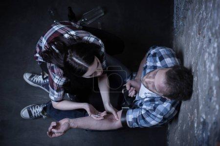 Toxicomanes utiles faire l'injection d'héroïne dans l'endroit sombre