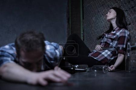 Desperate drug addict lying on the floor in the basement