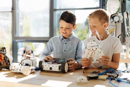 Foto de Amantes de la tecnología. Dulce los niños sentado en la mesa y el escrutinio recién construidos robots, uno de ellos sosteniendo un robot Guerrero, mientras que el otro examen de coche robótica - Imagen libre de derechos