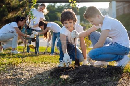 Photo pour Déterrer. Enfants se livrant à la plantation d'arbres et d'aider les uns les autres, en gardant le sourire sur leurs visages. - image libre de droit