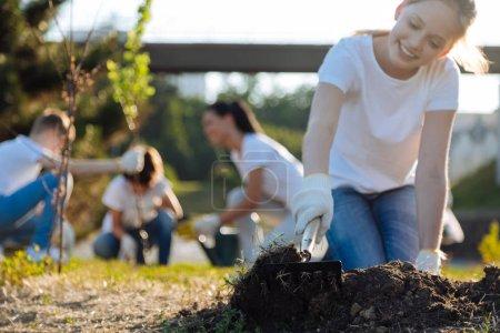 girl raking up soil for plants