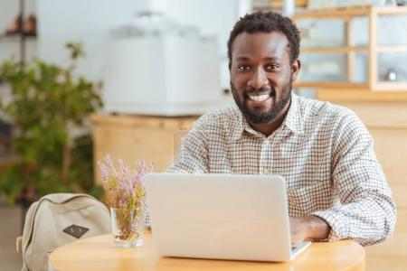 Upbeat man posing while working on laptop in cafe