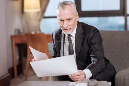 Senior experienced businessman  looking through documents