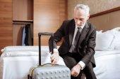 Senior focused man  locking luggage