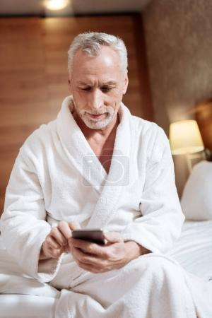Calm senior man typing letter