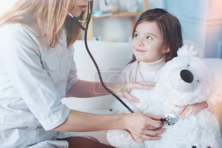 Serious nurse using stethoscope for measuring pressure