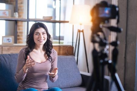 Photo pour Blog vidéo. Positif ravi femme joyeuse regardant dans la caméra et raconter son histoire tout en menant un blog vidéo - image libre de droit