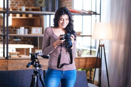 Cheerful delighted woman holding a camera