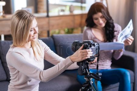 Photo pour Matériel de photo. Ravi positive belle femme en regardant la caméra et souriant tout en mise en place - image libre de droit