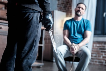 Cruel criminal holding a knife in his hand