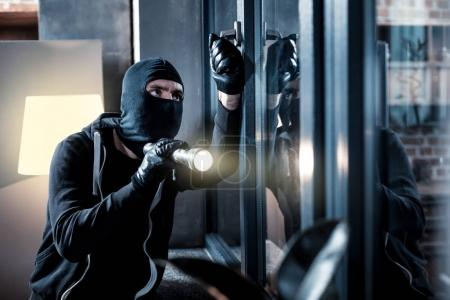 Masked burglar breaking into the house