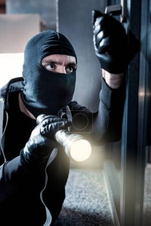 Masked thief breaking into the house