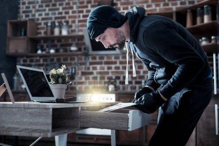 Skilful burglar looking for documents