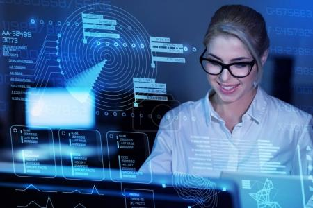 Photo for Working. Smart reliable qualified programmer dealing with important cyber security while being in her modern office and looking at the transparent screen of a new computer - Royalty Free Image