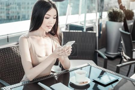 Young calm girl holding cellphone and looking at the screen.