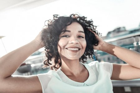 Photo for Grate day. Satisfied joyful cute girl holding hands behind her head smiling and standing on the rooftop. - Royalty Free Image
