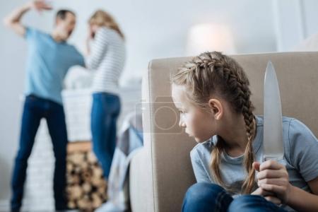 Terrified little girl holding a knife