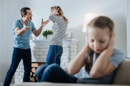 Photo pour Une famille malheureuse. Petite fille aux cheveux blonds sans sourire fermant les oreilles et assise sur le canapé pendant que ses parents se crient dessus - image libre de droit