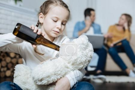Sad girl giving beer to her teddy bear