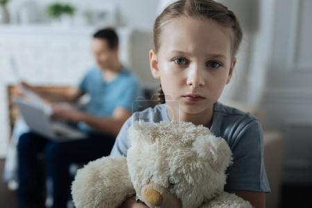 Triste niña sosteniendo su juguete