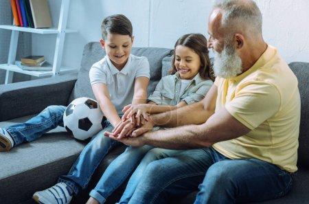 Photo pour Un pour tous et tous pour un. Joyeux petit garçon et petite fille souriant assis sur un canapé avec leur grand-père et joignant leurs mains ensemble pour la motivation . - image libre de droit