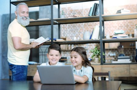 Mindful granddad looking at kids playing on laptop