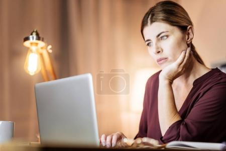 Thoughtful young woman staring at computer