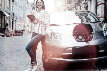 Joyful millennial girl using tablet while charging her electric car