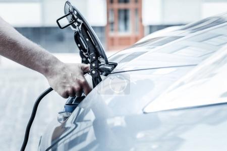 Primer plano de la mano masculina sosteniendo la boquilla de carga del coche eléctrico