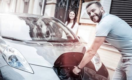 Hombre de mente positiva sonriendo mientras carga su coche respetuoso con el medio ambiente