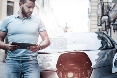 Tipo inteligente millennial que mira la boquilla de carga mientras carga energía