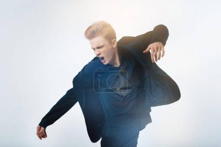 Photo pour Im une rock star. Satisfait bel homme élégant debout dans l'allégresse de salle spécieuses et gesticulant. - image libre de droit