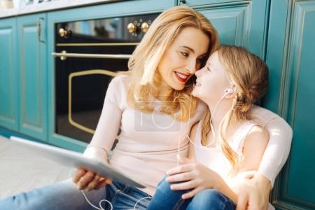 Cheerful mother and daughter listening to music
