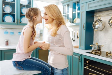 Content mother holding hands with her daughter
