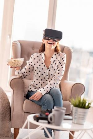 Happy joyful woman watching VR comedy