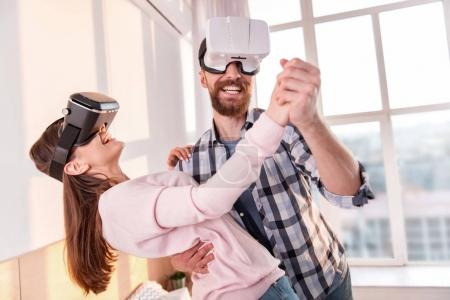 Attractive pleased couple circling in VR