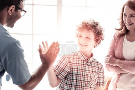Positive minded boy and medical worker high fiving