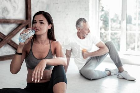 Beautiful brunette drinking water during training session