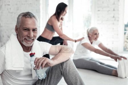 Confident elderly man drinking water after gym session