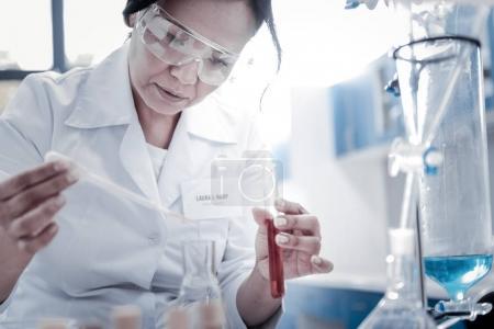 Focused female scientist mixing liquids in laboratory