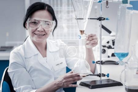Positive minded chemist smiling cheerfully while conducting experiment