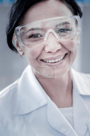 Beautiful woman wearing safety glasses smiling into camera