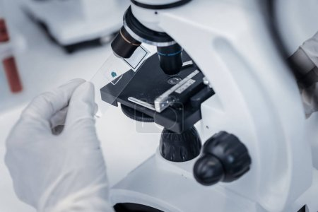 Close up of researcher placing sample under microscope