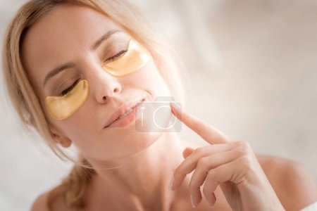 Nice relaxed woman using eye patches