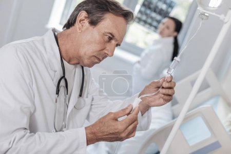 Concentrated physician checking drop counter in hospital