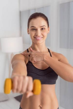 Smiling woman holding a hand weight in front of her