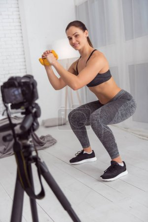 Joyful blogger squatting with hand weights for cam