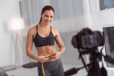 Happy blogger measuring her waist while making a video