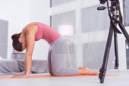 Delighted sportswoman exercising on her carpet