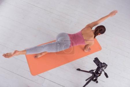 Muscular female blogger doing sport for camera